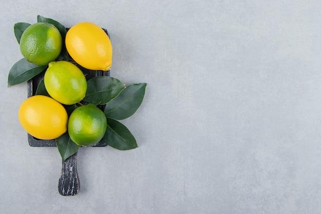 Limões verdes e amarelos em uma tábua de corte preta