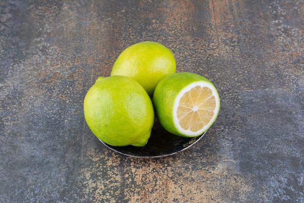 Limões verdes em um pires metálico em superfície rústica