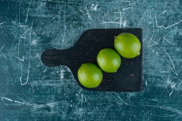 Limões verdes em uma placa de corte, na mesa de mármore.
