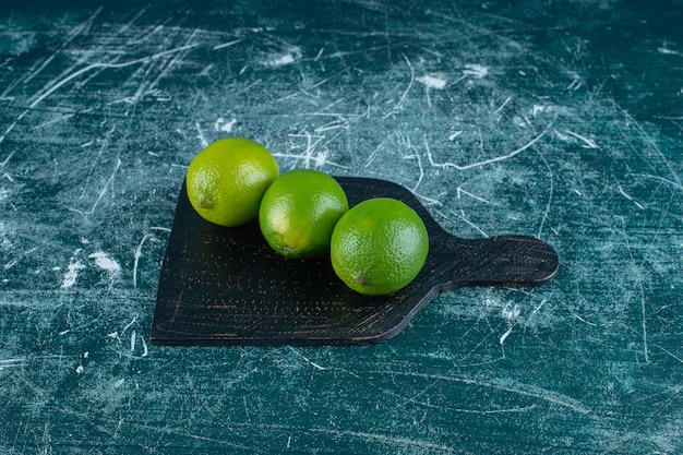 Limões verdes em uma placa de corte, no fundo de mármore. foto de alta qualidade