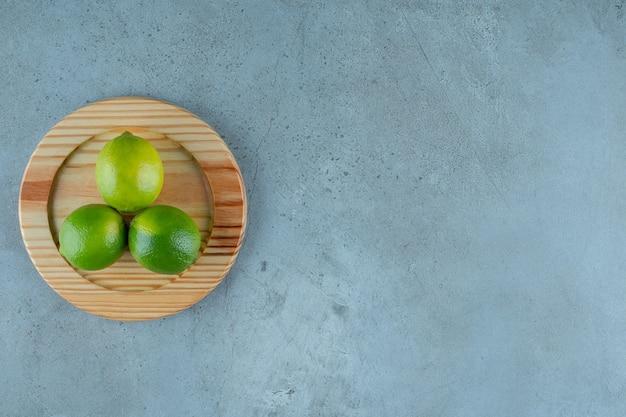 Limões verdes em uma placa de madeira, na mesa de mármore.