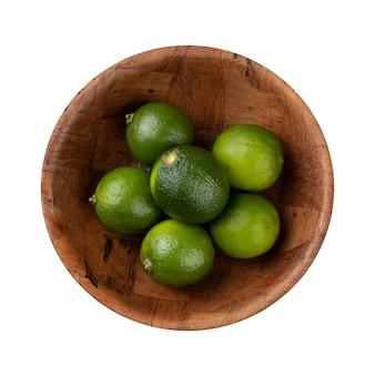 Limões verdes em uma tigela isolada no fundo branco.