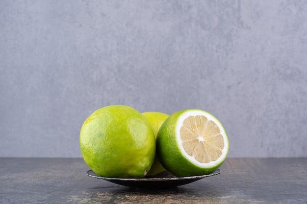 Limões verdes isolados em um mini pires preto