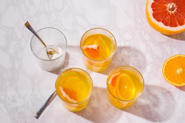 Limonada. beba com laranja fresca, limão e toranja. coquetel de limão com suco. limonada cítrica em copo. Foto Premium