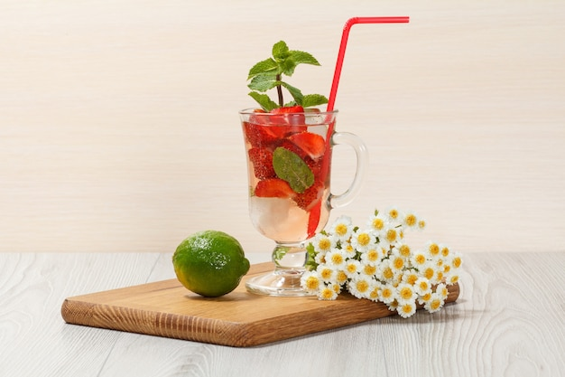 Limonada carbonatada com fatias de morango e hortelã em uma tábua de madeira, bebida gelada para um dia quente de verão