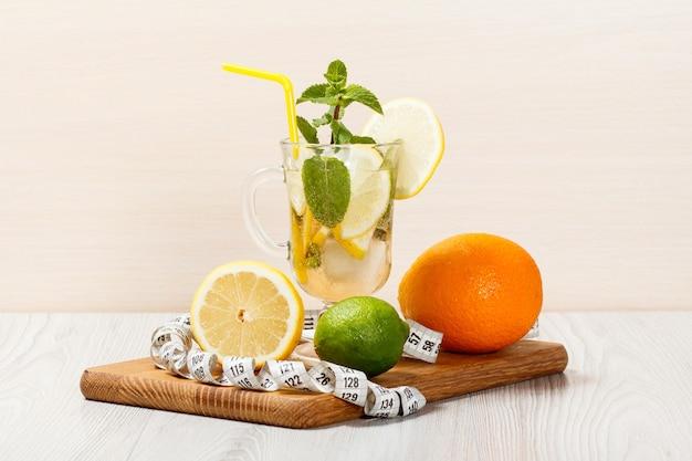 Limonada carbonatada com rodelas de limão e hortelã em uma tábua de madeira, bebida gelada para um dia quente de verão
