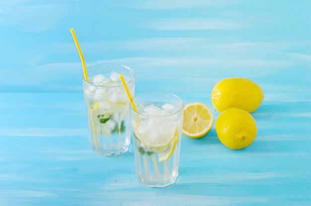 Limonada caseira com canudos para beber limão, hortelã, gelo e água em copos