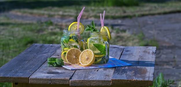 Limonada caseira com limão, hortelã e gelo em copos, na mesa de madeira, ao ar livre.