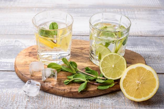 Limonada caseira com limão, limão, hortelã e cubos de gelo na luz cinza fundo de madeira.