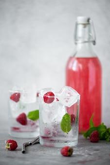 Limonada caseira de framboesa em uma garrafa e copos com gelo em uma mesa branca