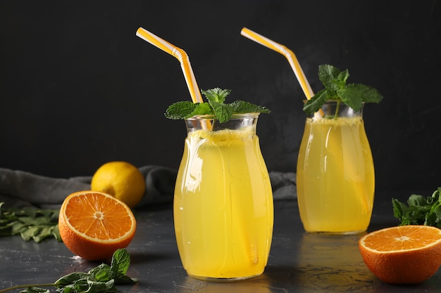 Limonada caseira de limões e laranjas, decorada com hortelã em copos altos com tubos na superfície escura, formato horizontal