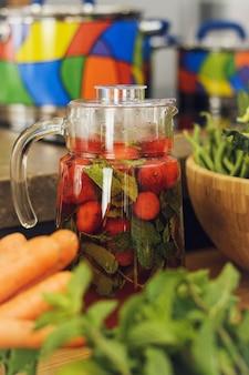 Limonada caseira de verão em cima da mesa entre frutas e legumes.