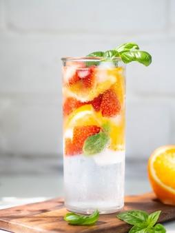 Limonada caseira de verão fresco com fatias de laranja, strawbereies, manjericão e gelo no copo sobre uma mesa branca.