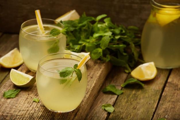 Limonada caseira em dois copos com canudos na mesa de madeira velha