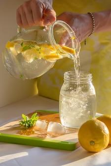 Limonada caseira fresca, despeje em um copo, desintoxicação, mão
