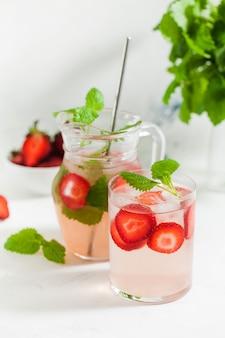 Limonada caseira refrescante de morango em copo e jarro com morangos frescos e folhas de hortelã bebida de verão