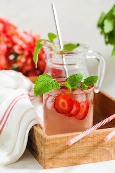Limonada caseira refrescante de morango em jarra e copo