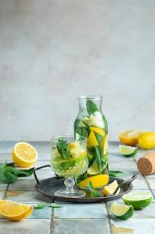 Limonada com limão e hortelã em jarra de vidro sobre ladrilhos