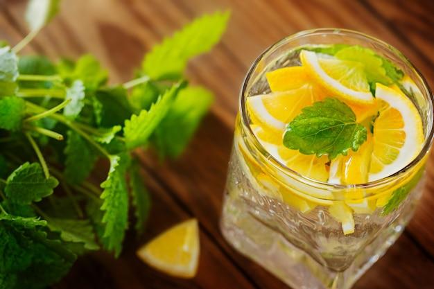 Limonada com limão fresco e hortelã no fundo de madeira