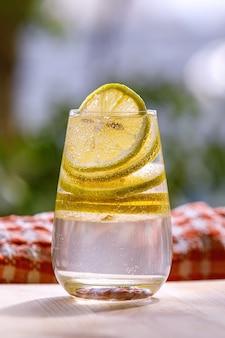 Limonada com limão fresco em copo no jardim