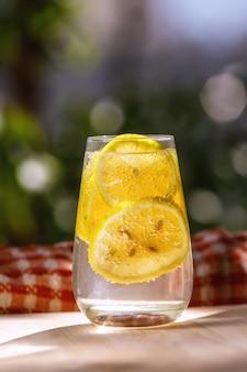 Limonada com limão fresco em vidro no jardim.