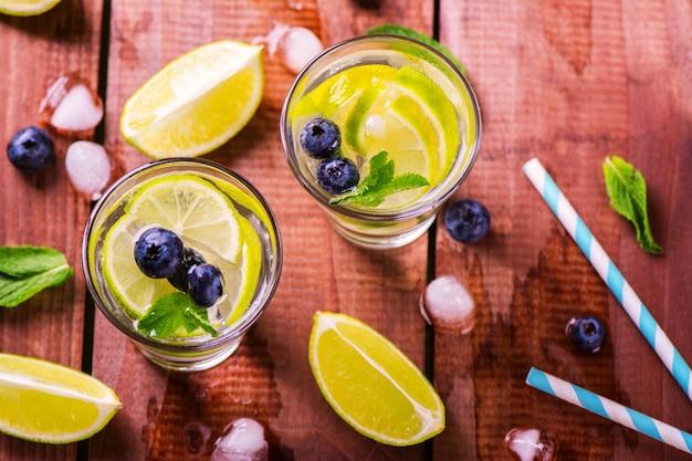 Limonada com limão fresco, frutas e hortelã no fundo de madeira
