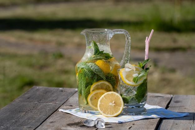 Limonada com limão, hortelã e gelo, em um jarro e um frasco, sobre a velha mesa de madeira, ao ar livre.