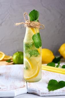 Limonada com limões, folhas de hortelã, limão em uma garrafa de vidro