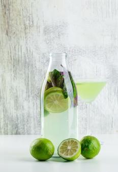 Limonada com limões, manjericão em garrafa e copo em branco e sujo,