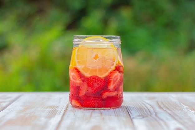 Limonada com morangos em uma jarra de vidro. bebida refrescante de verão.