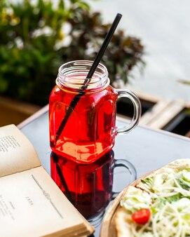 Limonada de baga na mesa no jarro de vidro com vista lateral para palha