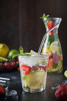 Limonada de desintoxicação com limão, laranja, limão, morango em copo e jarra.