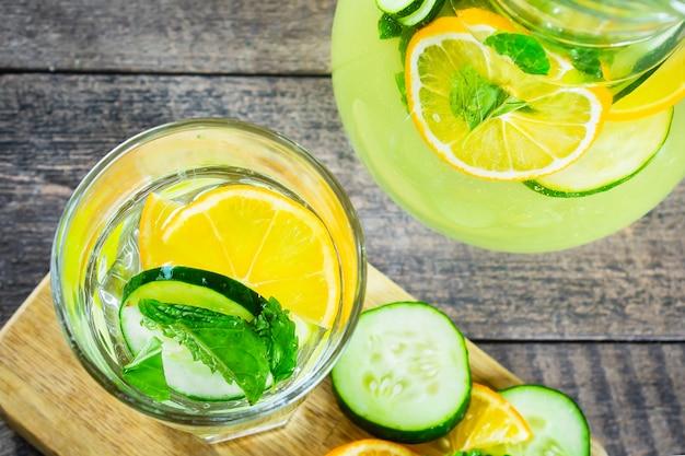 Limonada de desintoxicação de verão com laranja, limão, pepino e hortelã em um copo sobre uma mesa rústica de madeira. vista do topo.
