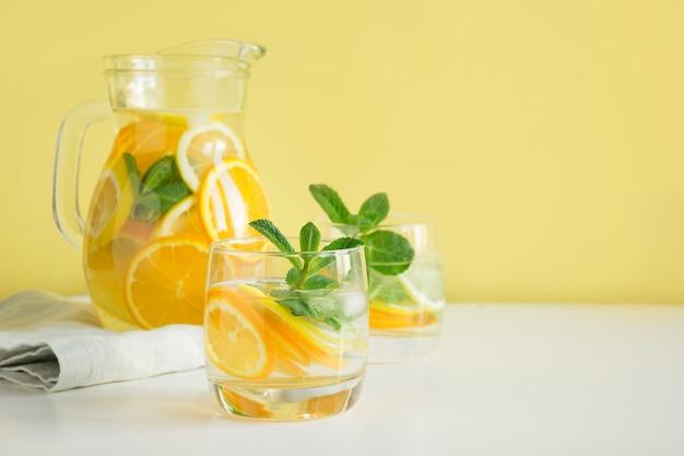 Limonada de desintoxicação de verão. molhe com limão, laranja, gelo e hortelã no copo.