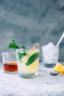 Limonada de gelo em copo com pedaços de limão, hortelã fresca e cubos de gelo