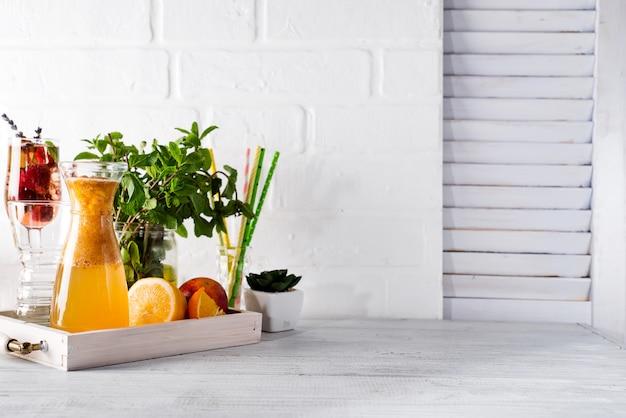 Limonada de laranja no decantador em uma bandeja de madeira com ftuits e hortelã