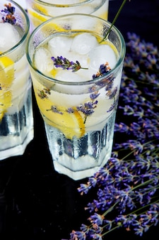 Limonada de lavanda com limão e gelo no preto.