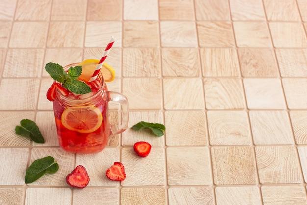 Limonada de morango com limão e gelo em um frasco de vidro sobre uma mesa de madeira