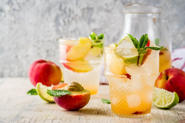 Limonada de pêssego e limão, mojito cocktail com enfeite de frutas frescas, no foco seletivo da luz superfície de concreto