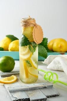 Limonada de refrigerante em uma garrafa de vidro e limões frescos maduros