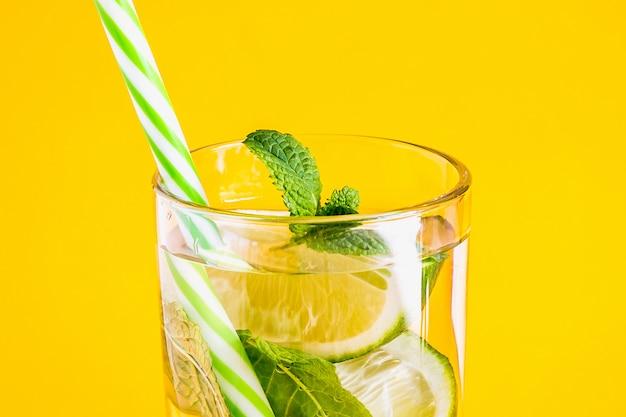 Limonada de verão com água, limão e hortelã em um copo de vidro com um canudo
