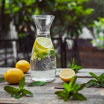 Limonada e ingredientes em um jarro de vidro na mesa de madeira e jardim, vista lateral.