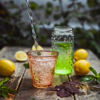 Limonada e ingredientes em vidro e jarra na mesa de madeira e quintal. vista lateral.