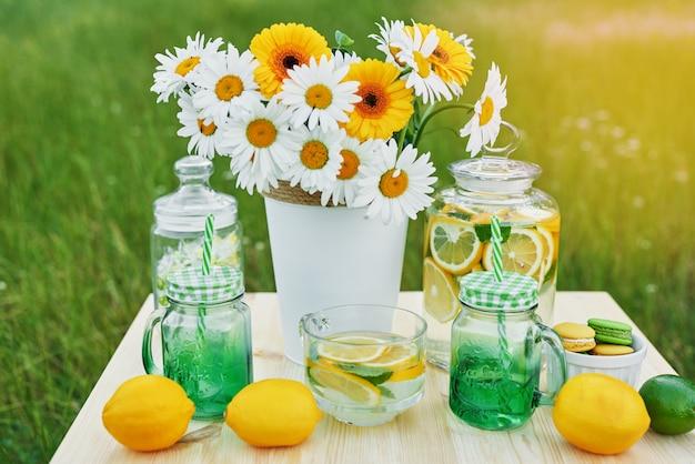 Limonada e margarida flores na mesa. mason jar copo de limonada com limões. piquenique ao ar livre.