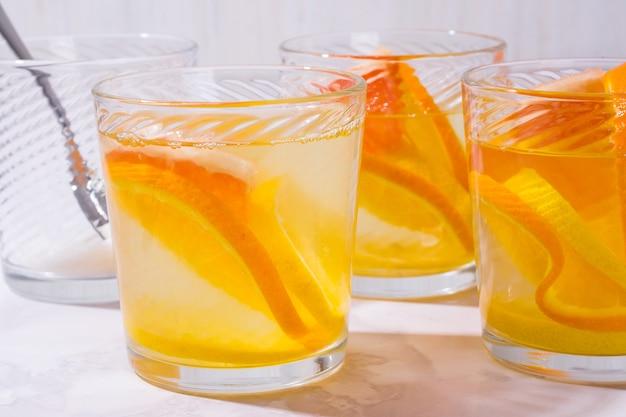 Limonada em copo com laranjas, limões e toranja em copos de mesa de limonada shot na mesa branca