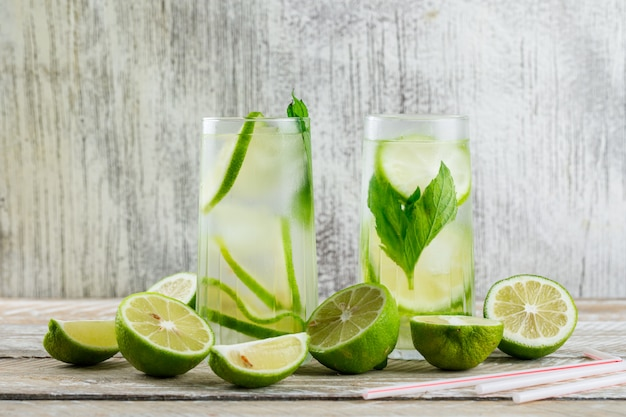 Limonada em copos com limão, manjericão, palhas vista lateral em madeira e sujo