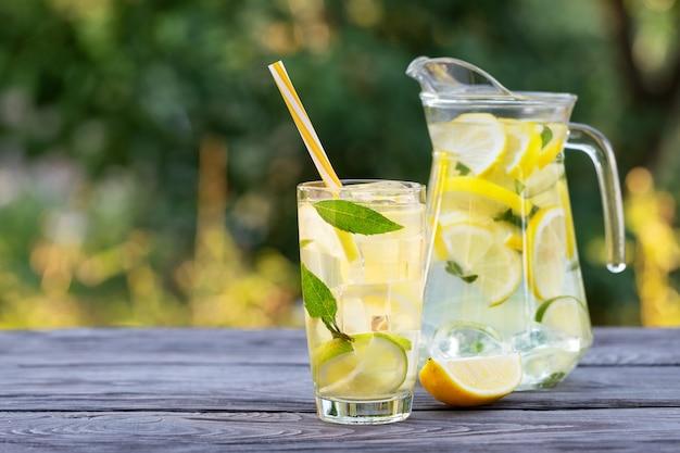 Limonada em jarra e copo e rodela de limão na mesa de madeira
