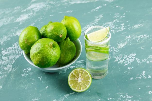 Limonada em um copo com limões vista de alto ângulo em um gesso