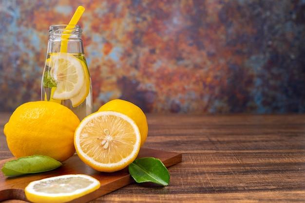 Limonada fresca, bebendo com ervas em vidro, limão ou mojito cocktail com limão na mesa de madeira para espaço de cópia e fundo de metal rústico grunge no verão quente