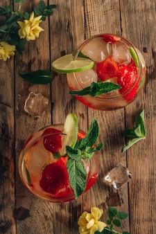 Limonada fresca com chá verde, lima, hortelã e morango no fundo de madeira, bebida fria de verão, dois copos com chá gelado de frutas vermelhas, vista superior
